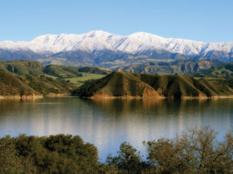Winter 2011 photo of a full Lake Cachuma with snowy peaks in the background.
